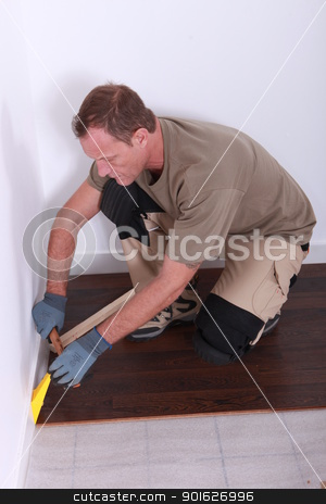 Man fitting a wooden floor stock photo, Man fitting a wooden floor by photography33