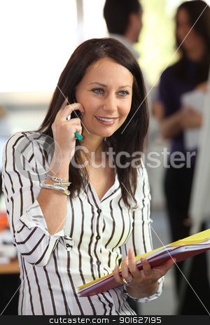 Woman on the phone holding office files stock photo, Woman on the phone holding office files by photography33