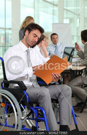 A group of business people in a meeting room, one of them in a wheelchair. stock photo, A group of business people in a meeting room, one of them in a wheelchair. by photography33