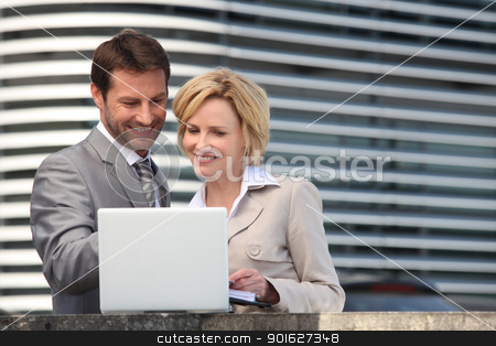 Businessman and woman looking at laptop stock photo, Businessman and woman looking at laptop by photography33