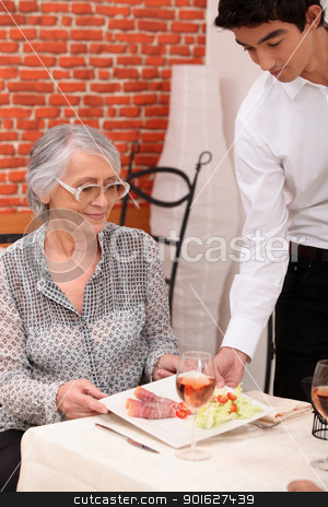 Young waiter serving lunch to an older customer stock photo, Young waiter serving lunch to an older customer by photography33