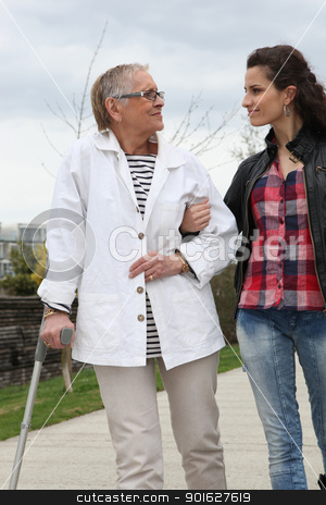 Young woman helping elderly person to walk with a crutch stock photo, Young woman helping elderly person to walk with a crutch by photography33