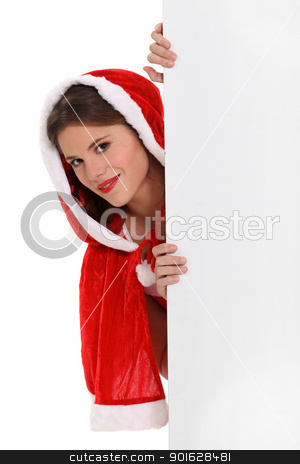 Miss Santa peeking round a board left blank for your message stock photo, Miss Santa peeking round a board left blank for your message by photography33