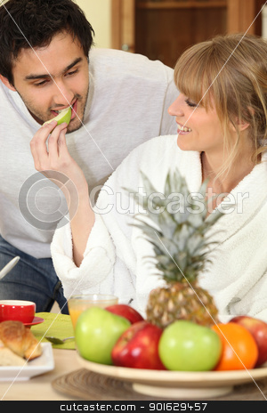 Young couple eating fruit at breakfast stock photo, Young couple eating fruit at breakfast by photography33
