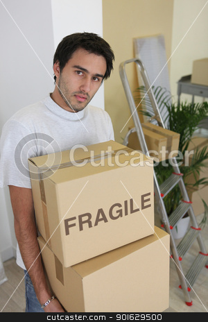 Young man carrying cardboard boxes on moving day stock photo, Young man carrying cardboard boxes on moving day by photography33