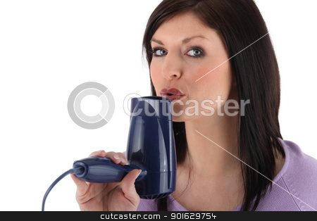 Woman blowing on a hairdryer stock photo, Woman blowing on a hairdryer by photography33