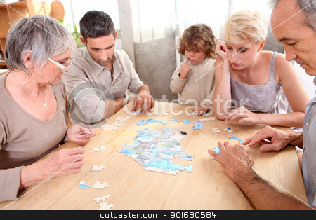 Family making puzzle stock photo, Family making puzzle by photography33
