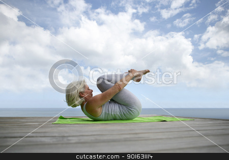 senior woman making exercises on the beach stock photo, senior woman making exercises on the beach by photography33