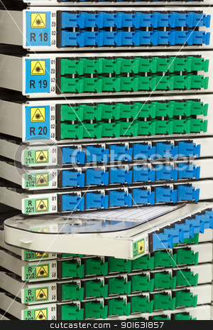 fiber optic rack with high density of blue and green SC connectors stock photo, fiber optic cable management system with green and blue SC connectors by Artush