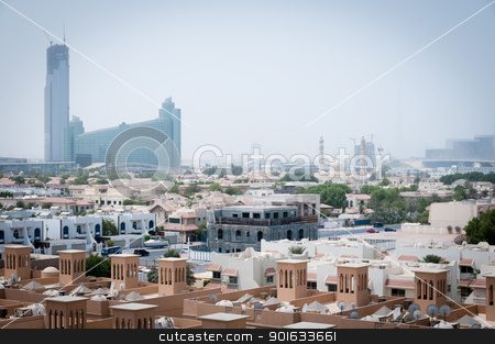 Dubai covered by sand haze stock photo, Dubai, UAE - August 29, 2011: The city covered by sand haze with skyscrapers and mosque on background and private buildings on the front. by Iryna Rasko