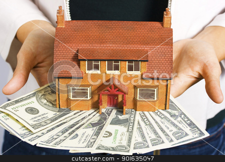 A person holding a miniature house and some dollar bills stock photo, A person holding a miniature house and some dollar bills for making payments by stuartmiles