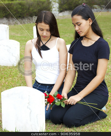 Two Sad Girls At A Grave stock photo, Two Sad Girls At A Grave Of Their Friend by stuartmiles