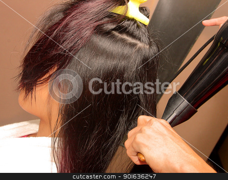 Stylist Using A Hair Dryer To Dry Hair stock photo, Stylist Using A Hair Dryer To Dry The Hair Of A Customer by stuartmiles