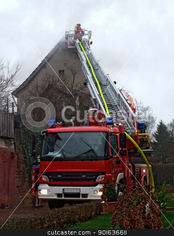 fireman on ladder stock photo, a burning house and firefighters at work in rainy ambiance at evening time by prill