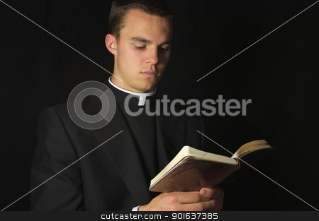 Priest with Prayer book stock photo, Young Priest in black reading prayer book by Gregory Dean