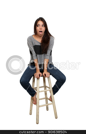 Casual Brunette on a Barstool (2) stock photo, A lovely young brunette in casual wardrobe, with a surprised or shocked facial expression, sits on a barstool, isolated on a white background with generous copyspace. by Carl Stewart