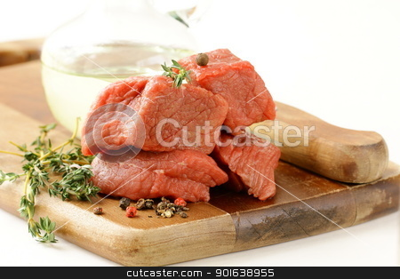 Fresh raw beef with thyme and spices on a cutting board stock photo, Fresh raw beef with thyme and spices on a cutting board by Olga Kriger