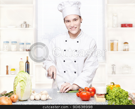 Young chef cutting onions in kitchen stock photo, Young female chef cutting onions in kitchen by iMarin