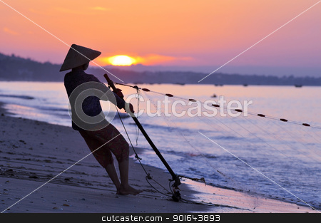 Silhouette of a fisherman stock photo, Silhouette of a fisherman on beach at sunrise by John Young