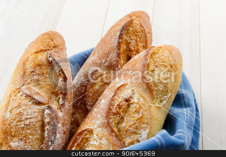 Crusty Artisan French Baguette Bread stock photo, Overhead view of three fresh baked crusty French Baguettes dusted with flour and wrapped in a blue towel by Karen Sarraga