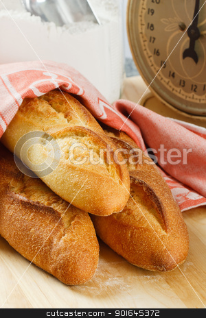 Three Fresh Baked Baguettes stock photo, Three loaves of fresh baked baguette bread with flour and scale in the background by Karen Sarraga