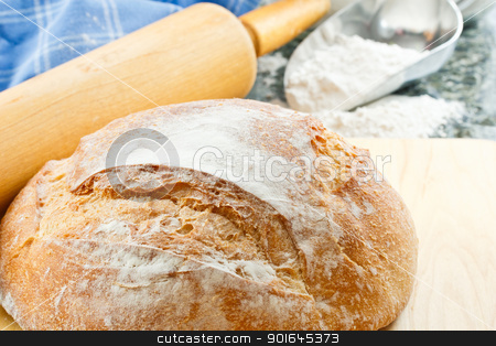 Close Up Of Fresh Baked Bread stock photo, Overhead view of fresh baked artisan bread with enriched wheat flour and rolling pin in the background by Karen Sarraga