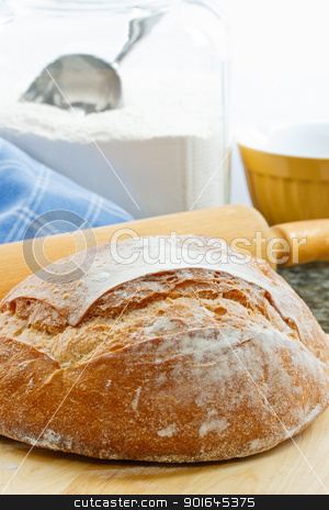 Fresh Baked Artisan Bread stock photo, Fresh baked round artisan bread with rolling pin and flour jar in the background by Karen Sarraga