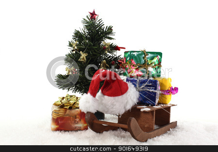 Sledge and gifts under the Christmas tree stock photo, Santa Claus hat and slide under the Christmas tree with colorful gifts by Maren Wischnewski