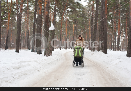 Young mother with baby carriage in winter forest stock photo, Young mother pushing pram in park on winter day by Aikon