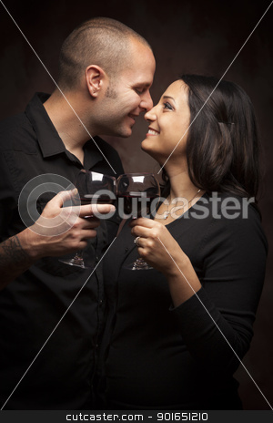 Happy Mixed Race Couple Flirting and Holding Wine Glasses stock photo, Happy Mixed Race Couple Flirting and Holding Wine Glasses on a Dark Background. by Andy Dean