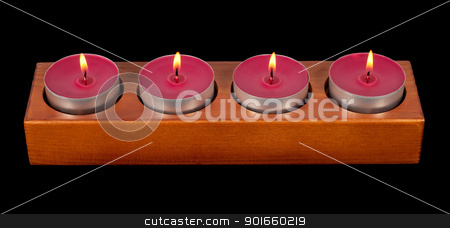Four burning candles stock photo, Wooden candleholder or candlestick with four burning or flaming  candles isolated on black  background by borojoint