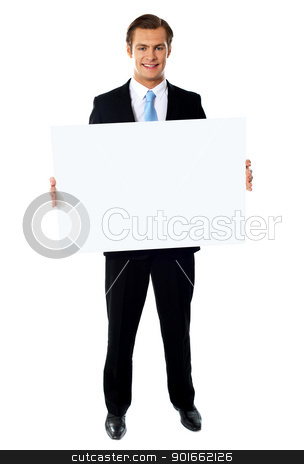 Portrait of businessman showing blank signboard stock photo, Portrait of smiling young businessman showing blank signboard by Ishay Botbol