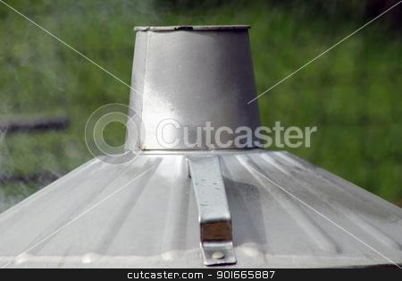 Metal incinerator stock photo, Top of metal garden incinerator billowing smoke. by Martin Crowdy