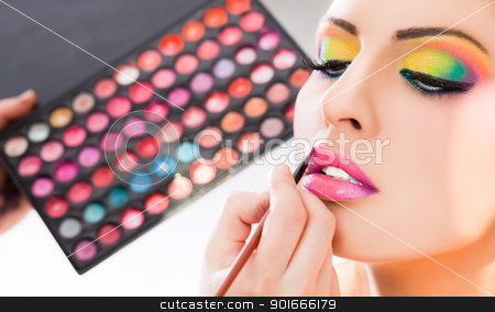 make-up lipstick stock photo, Beautiful woman having lipstick applied by make-up artist by vilevi