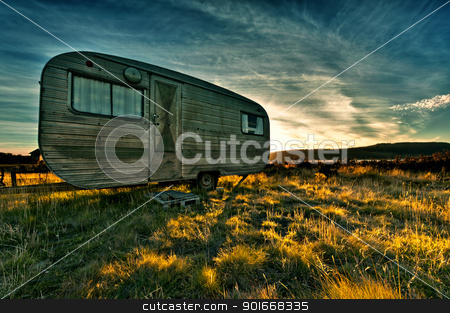 Camper trailer backlit by the sun during a beautiful sunset stock photo, Camper trailer backlit by the sun during a beautiful sunset by Ulrich Schade