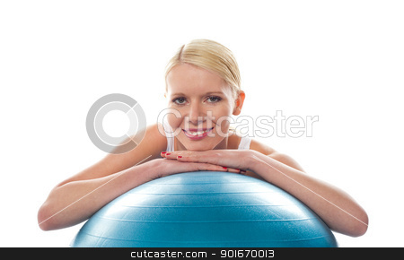 Attractive fit young woman resting chin over ball stock photo, Attractive fit young woman resting chin over ball isolated against white background by Ishay Botbol
