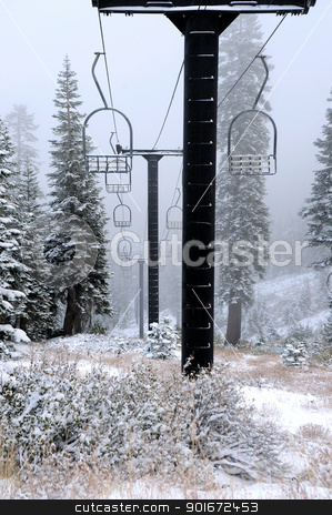 Old Abandoned Ski Lift stock photo, Old ski lift pylons with cables and chairs disappear into a snow covered forest by Lynn Bendickson
