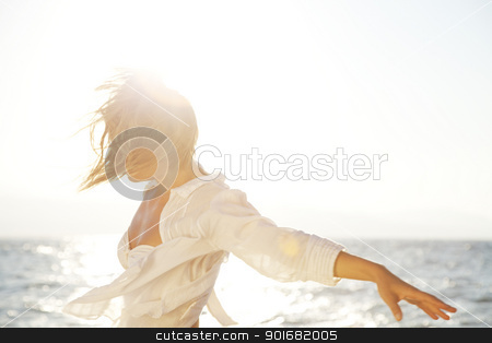 freedom stock photo, carefree young woman on a windy beach by Liv Friis-Larsen