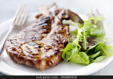 pork chop stock photo, juicy grilled pork chop (neck cut) with greens by Liv Friis-Larsen