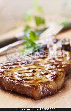 pork chop stock photo, juicy grilled pork chop (neck cut) with greens by Liv Friis-Larsen