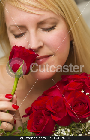Woman Smelling a Bunch of Red Roses stock photo, Beautiful Woman Smelling a Bunch of Red Roses. by Andy Dean