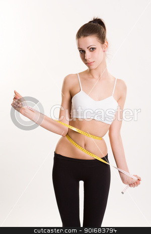 Super slim. stock photo, Beautiful skinny young brunette getting tied up in measuring tape. by exvivo