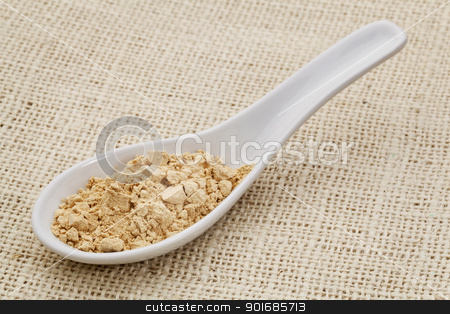 maca root powder on a ceramic spoon stock photo, ceramic tablespoon of maca root powder (dietetary supplement) against burlap canvas by Marek Uliasz
