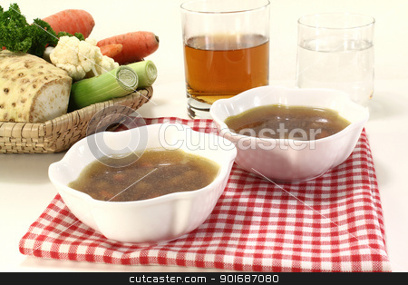 Beef consomme stock photo, Beef consomme with root vegetables with a glass of juice and water by Maren Wischnewski