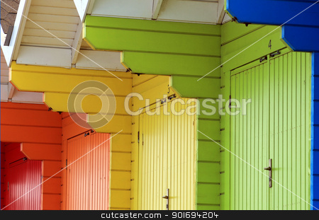 Colorful beach chalets or huts stock photo, Row of colorful beach chalets or huts, abstract background. by Martin Crowdy