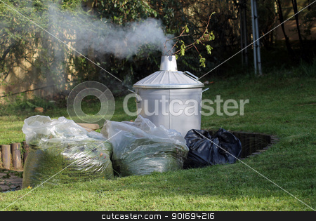 Garden incinerator stock photo, Garden incinerator next to bags of cut grass, lawn in foreground. by Martin Crowdy