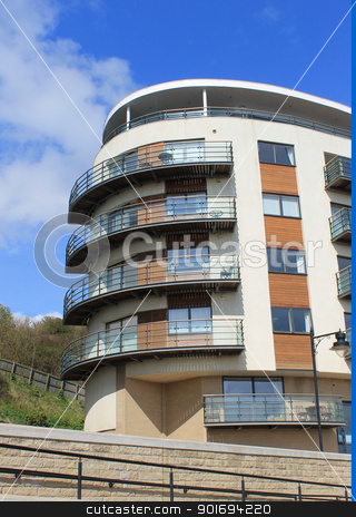 Modern apartment building stock photo, Exterior of curved modern apartment building with blue sky background and copy space. by Martin Crowdy