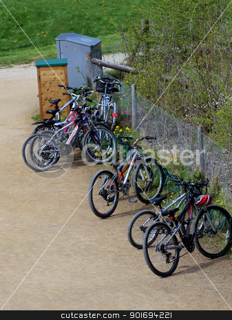 Mountain bikes in countryside stock photo, Row of mountain bikes parked in countryside on path or track. by Martin Crowdy