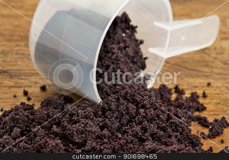 dried acai berry powder stock photo, dried acai berry powder spilling of a plastic measuring scoop against grunge wood background by Marek Uliasz