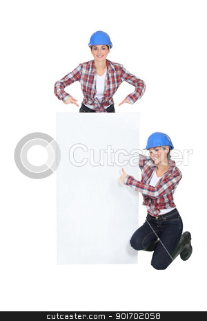 Female builder in front of blank poster stock photo, Female builder in front of blank poster by photography33